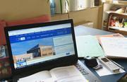 Home-Office: Notebook, Geschäftsunterlagen und Schulaufgaben der Kinder auf einem Tisch in der Küche
